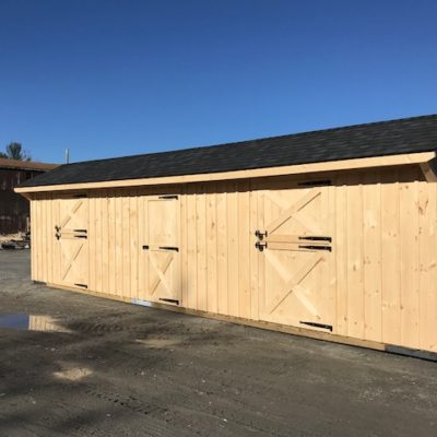 Natural wood two stall horse barn with tackroom.